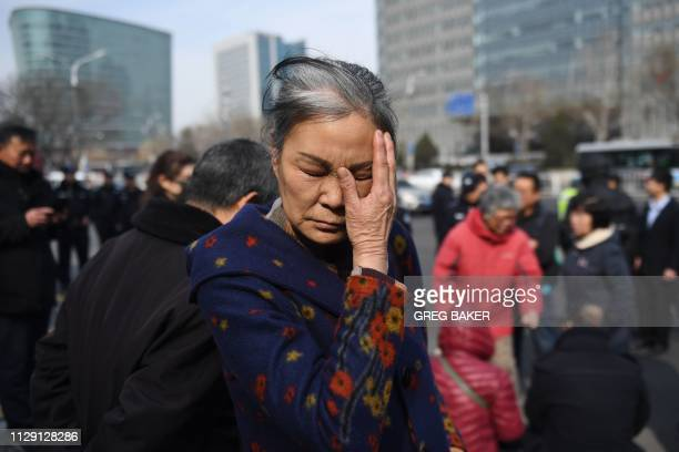 Relative of passengers of missing Malaysia Airlines flight MH370 cries outside the Foreign Ministry in Beijing on March 8, 2019. - Relatives gathered...