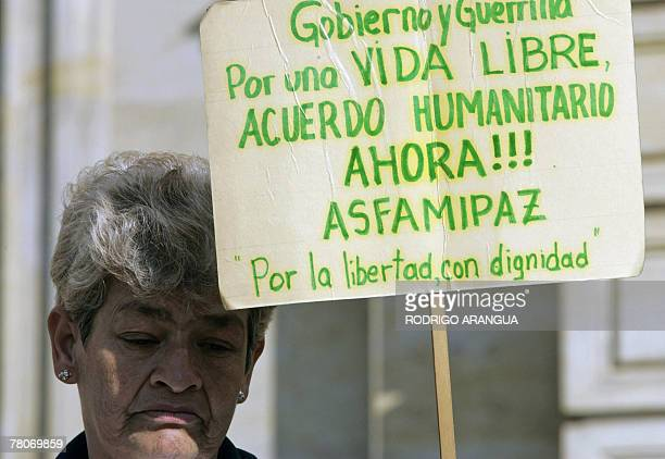 A relative of people kidnapped by the guerrillas FARC holds a sign asking for a humanitarian agreement during a protest 22 November 2007 in front of...