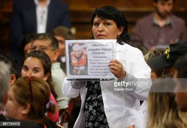 A relative of Senior Corporal Leandro Cisneros holds a sign with his picture during a meeting held by the FPVPJ Parliamentary Group with ARASan...