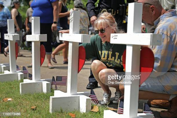 A relative of shooting victim Michelle 'Missy' Langer kneels at a cross with her name on it at a makeshift memorial site at the city Municipal Center...