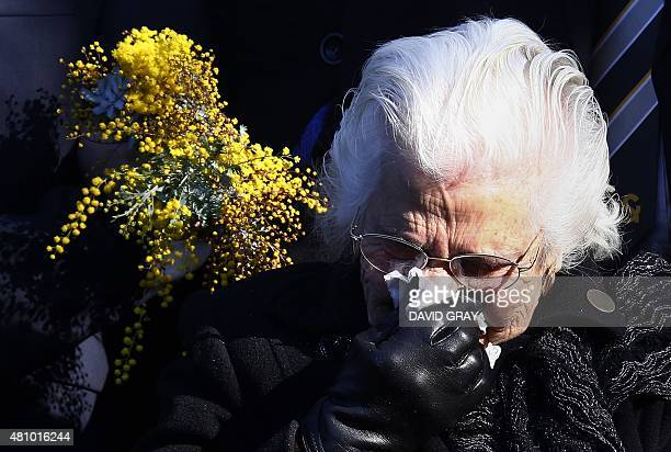 A relative of the Australian victims of Malaysia Airlines flight MH17 reacts before placing a floral tribute at a memorial that was unveiled on the...