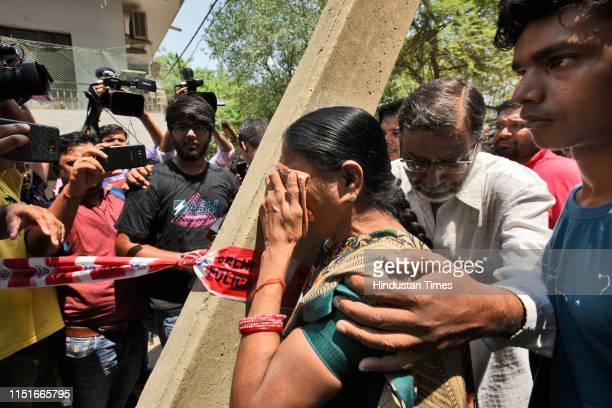 Relative of the elderly couple weeps after they were found murdered in their house along with their domestic help, at Vasant Apartments, in Vasant...