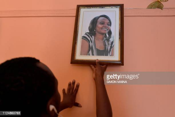 A relative of the late Kenyan human rights activist Caroline Mwatha hangs her framed portrait at her house in Dandora in the ouskirts of Nairobi on...