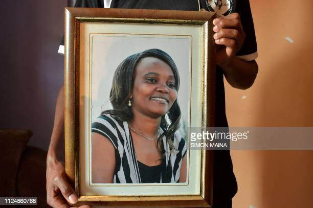 A relative of the late Kenyan human rights activist Caroline Mwatha hangs her framed potrait at her house in Dandora in the ouskirts of Nairobi on...