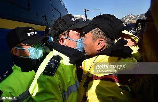 A relative of the victims of South Korea's Sewol ferry disaster is in a nosetonose standoff with a policeman during an antigovernment protest near...