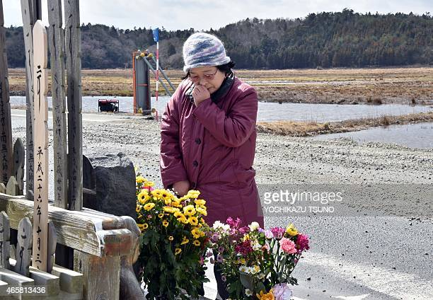 A relative of tsunami victims offers a flower bouquet at the altar at Namie near the striken TEPCO's Fukushima Daiichi nuclear plant in Fukushima...
