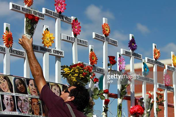 Relative of victims of the Casino Royale puts flowers on a cross during the commemoration of the first anniversary of the crime in Monterrey, Mexico,...