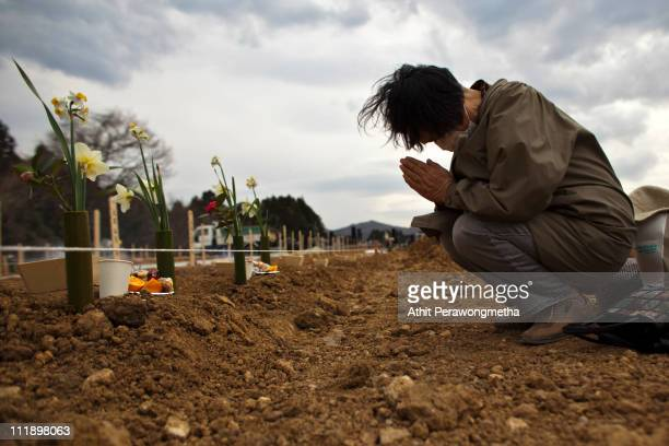 A relative pays her respects to an earthquake victim on April 8 2011 in Yamamoto Miyagi Prefecture Japan The 90 magnitude strong earthquake struck...