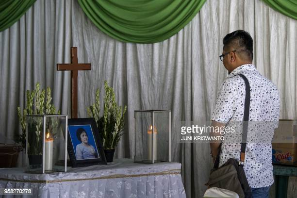 A relative pays his last respects to Sri Puji one of the victims killed during the May 13 Pantekosta church attack ahead of her funeral in Surabaya...