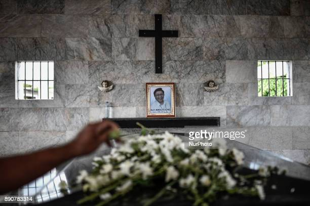 A relative places a flower on the tomb of activist priest Fr Marcelito quotTitoquot Paez following his funeral in San Jose Nueva Ecija north of...