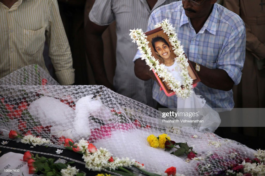 A relative places a photo of H.Gloria, an Air India Express crash victim, onto her coffin during her funeral service, at the St. Alphonsa Catholic Church, on May 23, 2010 in Mangalore. H.Rosaline and her two daughters H.Goldine and H.Gloria were passengers of the Air India Express Boeing 737-800 series aircraft arriving from Dubai, with 166 people onboard. Airline officials say 8 survivors have been rescued with 158 others feared dead.