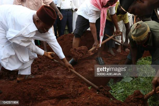 TOPSHOT A relative pour sand on the grave of the deceased of the two Air Force pilots killed in a fighter jet crash in Abuja on September 28 2018...