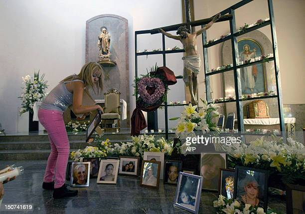 Relative puts the portrait of a victim of the Casino Royale on the floor during a mass commemorating the first anniversary of the crime in Monterrey,...
