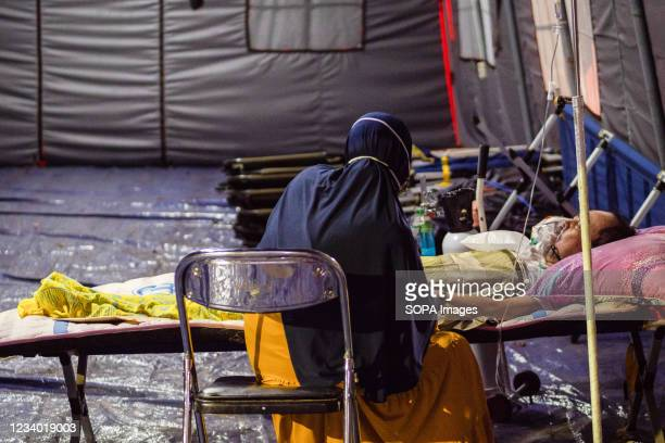 Relative sits beside her Covid-19 patient who is breathing through an oxygen mask outside Bekasi Public Hospital. Hospitals in Java, Indonesia are...