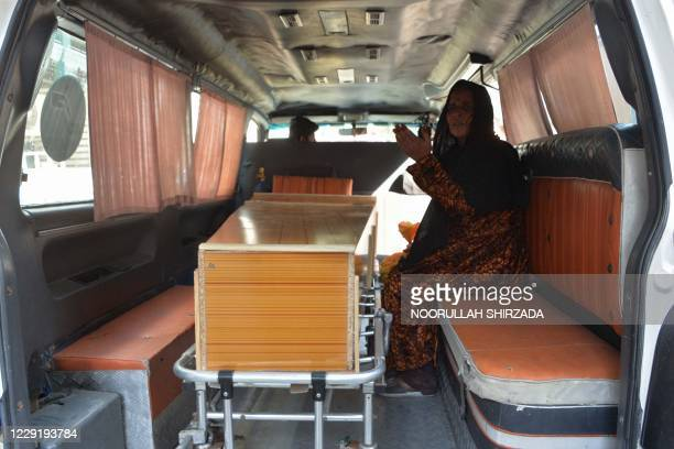 Relative sits next to the coffin of a victim, who was killed in a stampede, in Jalalabad on October 21, 2020. - At least 11 women were killed on...