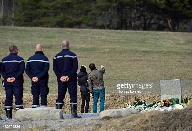 A relative stands at a monument to honour the victims of Germanwings flight 4U9525 in front of the mountains near the crash site on March 26 2015 in...