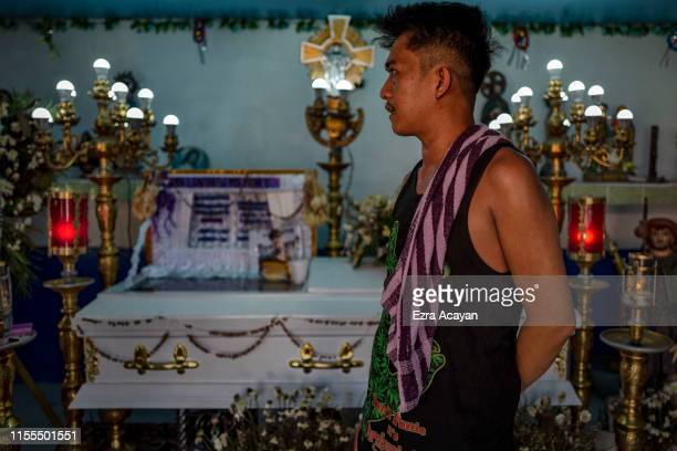 A relative stands next to the coffin of Ricky Adarayan on July 13 2019 in Malabon Metro Manila Philippines According to relatives say Adarayan was...