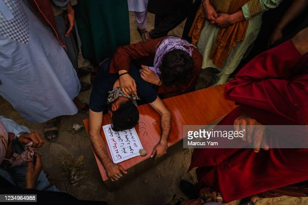 Relative throws himself and weeps over the casket of Farzad who was killed by U.S. Drone airstrikes, according to the family, in Kabul, Afghanistan,...