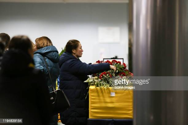 Relative to a victim lays flowers at the Boryspil International Airport during the memorial ceremony. Bodies of 9 crew members and 2 passengers were...