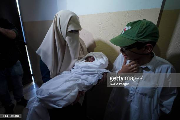 A relative to the deceased seen carrying the body during the funeral of Maria alGazali a fourmonthold Palestinian baby who was martyred in an Israeli...