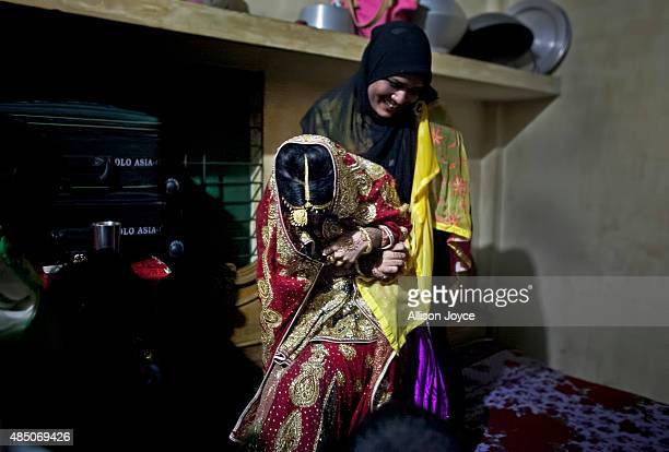 A relative tries to drag 15 year old Nasoin Akhter onto a bed to pose for photographs on the day of her wedding to a 32 year old man August 20 2015...