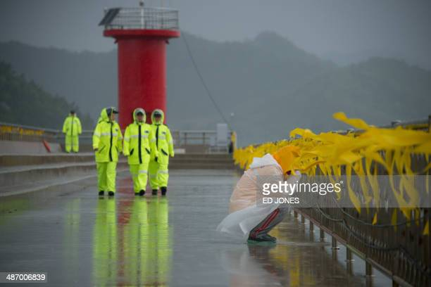 A relative weeps before yellow ribbons at Jindo harbour where relatives of family members of the 'Sewol' ferry are waiting for developments in the...