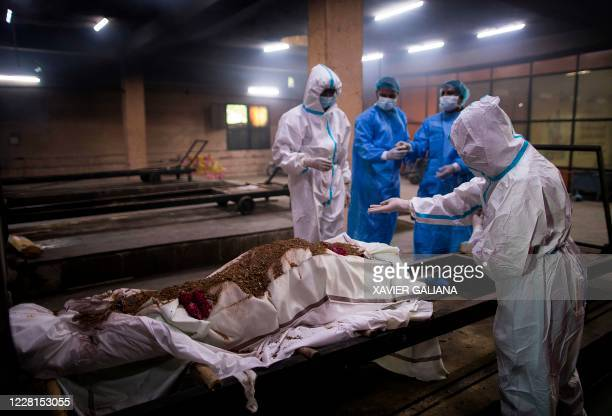 Relatives along with workers wearing Personal Protective Equipment prepare the body of a person who died from the COVID-19 coronavirus before...