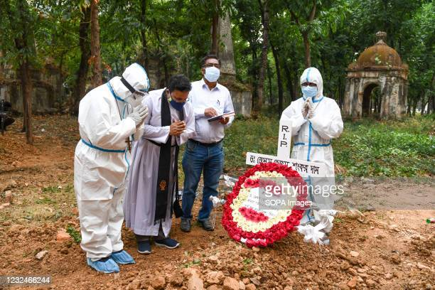 Relatives and a priest praying at the grave of the covid 19 deceased man, during a burial by Bangladeshi Christians at a cemetery.