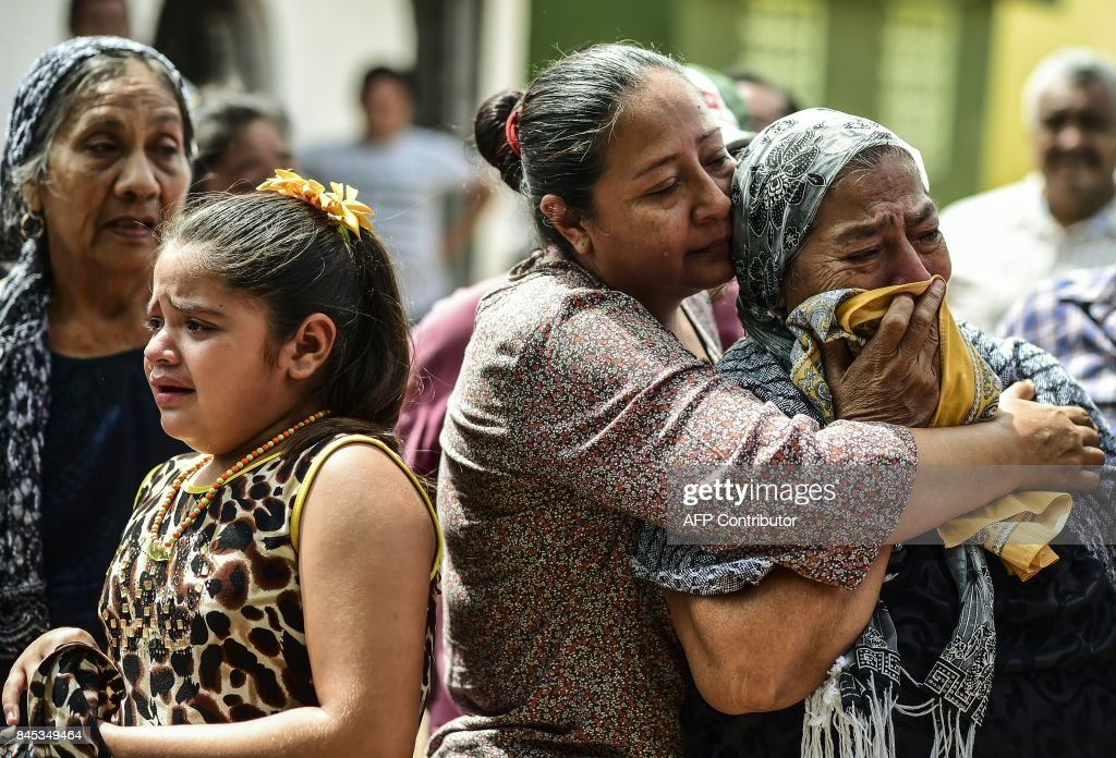 TOPSHOT - Relatives and friends accompany to the cemetery the remains of a victim of Thursday night's 8.2-magnitude quake, in Juchitan, Oaxaca, Mexico, on September 10, 2017. Rescuers pulled bodies from the rubble and grieving families carried coffins through the streets Saturday after Mexico's biggest earthquake in a century killed 65 people. /