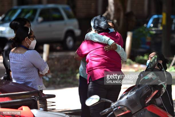 Relatives and friends embrace as they wait for the remains of murdered Honduran journalist Luis Almendares, outside the Forensic Medicine Board...
