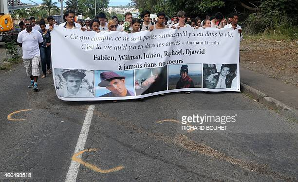 Relatives and friends hold a banner displaying the portraits of Fabien Wilman Julien Raphael and Djawid as 400 people attend a march on December 15...