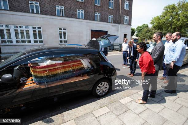 Relatives and friends look on as the willow eco coffin of Jon Underwood lies in an electric hearse following the funeral at the Jamyang Buddhist...