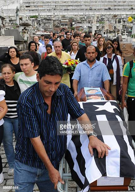 Relatives and friends of Air France cabin chief Brazilian Lucas Gagliano accompany his coffin covered with Gagliano's much cherished football team...