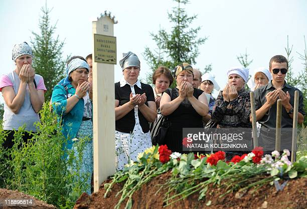 Relatives and friends of Faina Valiullina one of the 116 people killed in the country's worst river disaster pray during her funeral ceremony outside...
