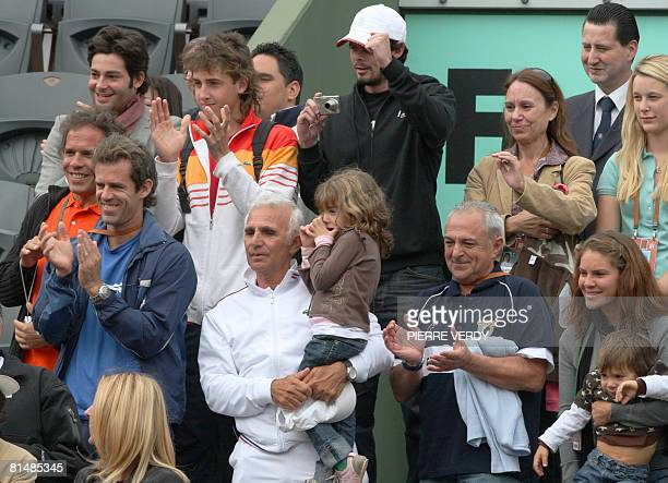Relatives and friends of Peruvian player Luis Horna and Uruguayan player Pablo Cuevas cheer during a match between Serbian player Nenad Zimonjic and...