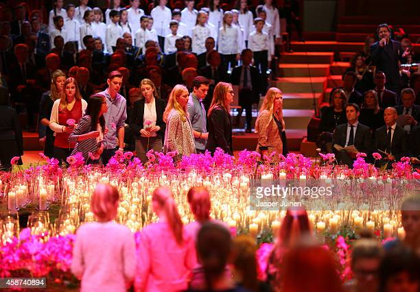 Relatives and friends of the victims of the Malaysia Airlines Flight 17 disaster place flowers around candles which represent the number of people...