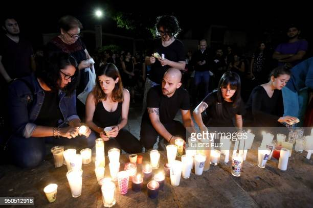 Relatives and friends of three missing students from the University of Audiovisual Media place candles during a demonstration to reject the official...