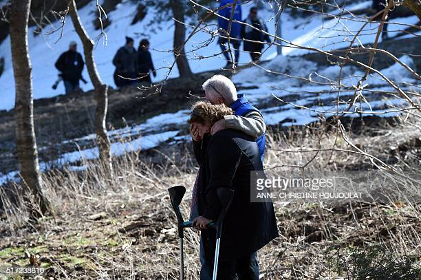 Relatives and friends of victims cry as they pay tribute at the Col Mariaud in Le Vernet southwestern France on March 24 in front of the mountain...