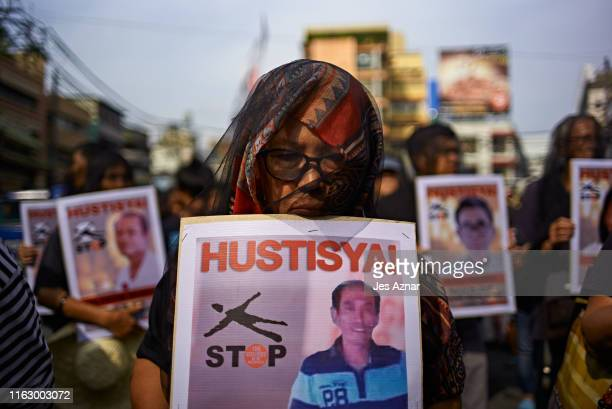 Relatives and friends of victims of extrajudicial killings hold pictures of their deceased kin as they participate in participate in a National Day...