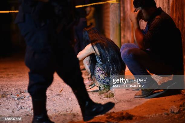 Relatives and friends stand mourn outside the place where 13 people were killed in a shooting, in Minatitlan, Veracruz State, Mexico on April 19,...