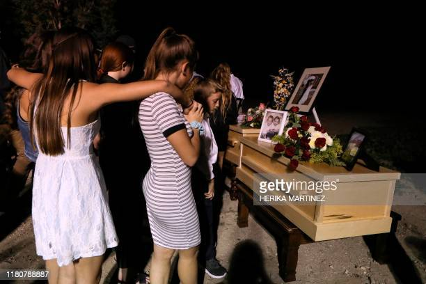 Relatives and friends stand next to the coffins with the remains of Rhonita Miller and four of her children who were among the nine victims killed on...