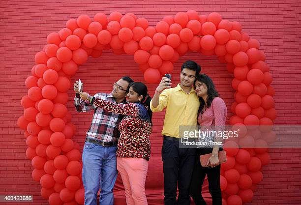 Relatives and friends take selfies in front of the heart shaped balloons as they celebrated Valentine's Day at The Great India Place mall on February...