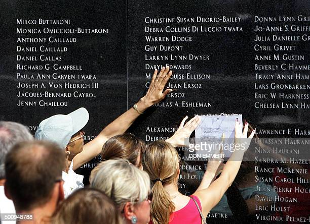 Relatives and friends touch and etch names on the memorial of TWA Flight 800 at Smith Point Park 17 July 2006 in Shirley New York The incident was...