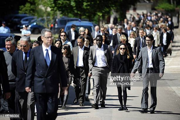 Relatives and friends walk to attend a burial service to the cemetery in NoyerssurSerein southern of Paris on April 30 after the private funeral...