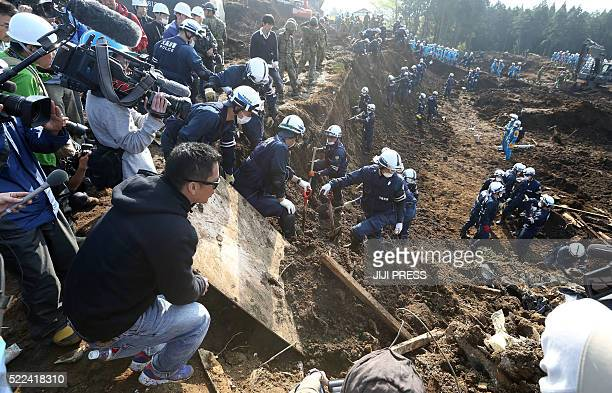 Relatives and journalists watch police officers search for missing victims in the village of Minami-Aso, Kumamoto prefecture on April 19, 2016. Two...
