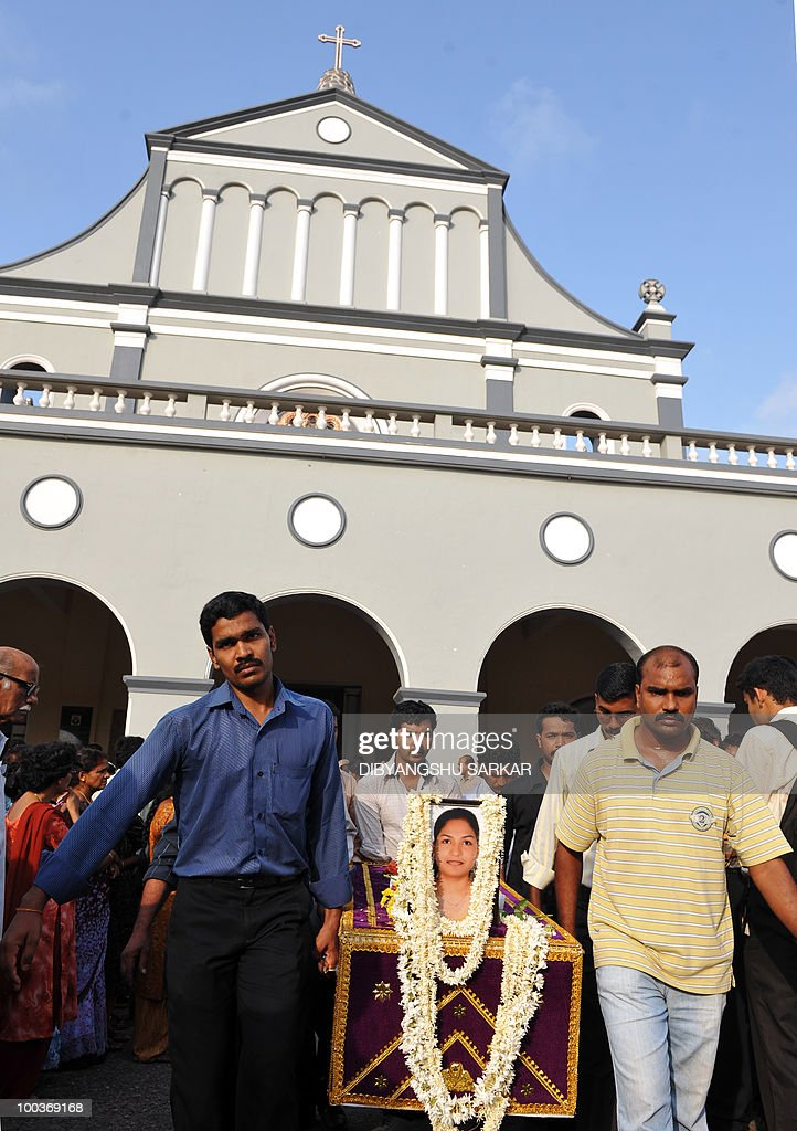 Relatives and mourners carry the coffin of Air India Express crash victims Savitha Philomene D'Souza (pictured) followed by her husband Naveen Walton Fernandes at the Holy Cross Church in Mangalore on May 24, 2010. Investigators on May 22 widened the search for the 'black box' data recorder of an Air India Express that crashed into a gorge killing 158 people, as the airline denied lax safety claims. AFP PHOTO/Dibyangshu SARKAR
