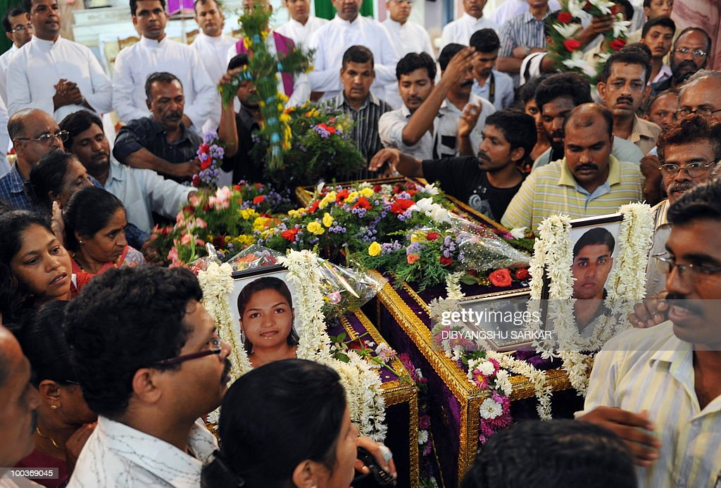 Relatives and mourners pay their last respects for Air India Express crash victims Naveen Walton Fernandes and his wife Savitha Philomene D'Souza at the Holy Cross Church in Mangalore on May 24, 2010. Investigators on May 22 widened the search for the 'black box' data recorder of an Air India Express that crashed into a gorge killing 158 people, as the airline denied lax safety claims. AFP PHOTO/Dibyangshu SARKAR