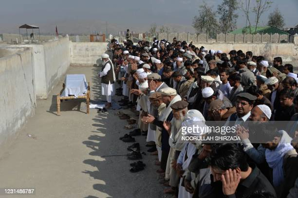 Relatives and mourners perform funeral prayers over the coffin of one of the three female media workers shot to death in two separate attacks, in...