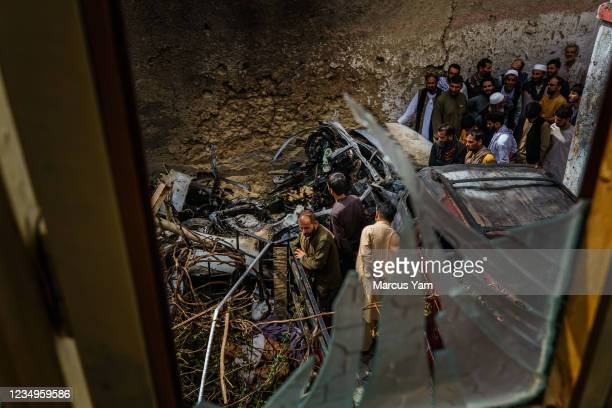 Relatives and neighbors of the Ahmadi family gathered around the incinerated husk of a vehicle targeted and hit earlier Sunday afternoon by an...