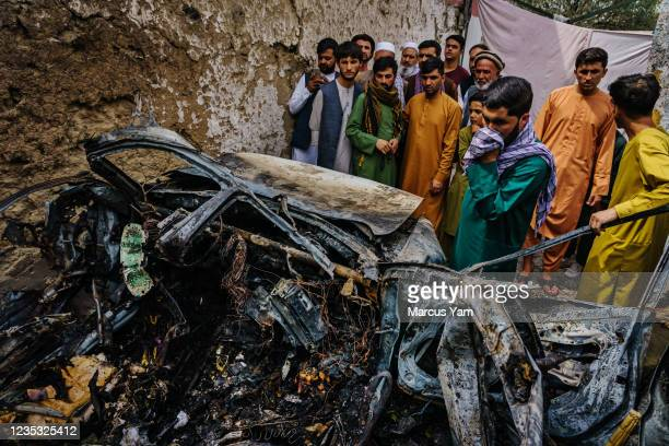 Relatives and neighbors of the Ahmadi family gathered around the incinerated husk of a vehicle targeted and hit by an U.S. Drone strike that was...